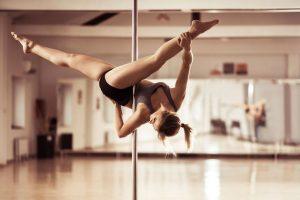 Ragazza pratica la pole dance in una palestra